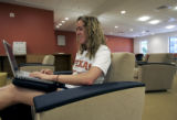 Senior, Erin Lowe checks her e-mail via wi-fi as she sits in the information commons in the The...