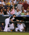 Rockies first baseman Jeff Baker tries to make a catch of a fly ball in the Rockies dugout  in the...