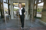 21310  Lawyer Jane Dickey holds open the glass doors at the Rose Law firm where she talks a little...