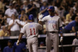 Chicago Cubs Jaque Jones is cheered on by Derrek Lee after Jones hit a solo home run in the 6th...
