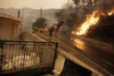 (NYT2) KARNASI, Greece -- Aug. 26, 2007 -- GREECE-FIRES-2 -- Panayiotis Panagopoulos hops over a...