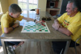 Colton Cardie (cq) plays checkers with his Grandpa, John Cardie (cq) in Arvada Sunday August...