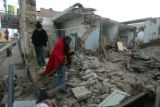 MM103 - A man cleans the debris at a house destroyed by an earthquake in Ica, southern Peru,...
