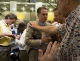 DLM0888  Pastor Brady Boyd, center, (facing camera with orange striped tie) prays with...