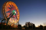 Lights glow in a time lapse photo of the Ferris Wheel as fairgoers wait beneath it for a turn on...