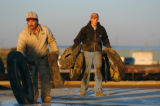 (IDALIA, Co., SHOT 10/7/2004) Scott Cure (right), 15, carries old tires to hold down a tarp that...