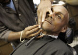 Edward Hatcher (cq) comes in once a month to get a shave from his barber Darryl Morgan (cq) at the...