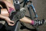 Rebecca Eckart (cq) of Golden, Colo., removes her shoes after her trail ride at Centennial Cone...