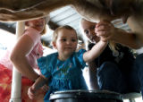 Eleanor Wingert, 2, center, gets help milking Nona, a cow owned by Diane Hanson (cq), right, while...