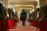 Retired Marine Corporal Kenn Gilchrist (cq) walks down a hall with the uniforms and photos of...