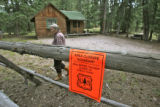 Charlotte Trego (cq) walks past a Forest Service sign on her 30-Mile Resort, Tuesday afternoon,...