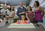 Twenty-four-year-old Brad Adams, middle, gets ready to blow out birthday candels with (left to...