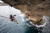Josh Lowell filming Chris Sharma rock climbing / deep water soloing on The Arch, his project in...