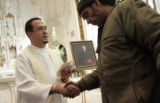 Father Feilx Zamora shakes the hand of a man who did not want to be identified during the annual...