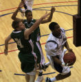 DM0002   Lincoln senior Kevin Carter drives to the basket past Smoky Hill senior Andy Setterlind,...