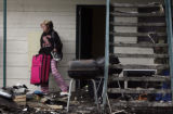 19 year-old Courtney Castillian (cq) walks out of her apartment with a few belongings after a fire...