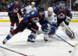 DXA104 - From left, Colorado Avalanche defenseman Karlis Skrastins, of Latvia, muscles out...