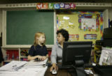 New Heights Academy principal Denise Duran talks over an assignment with second grader Kendra...