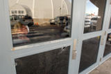 Church overseer Rev. Mike Ware photographs the bullet-riddled entryway of the New Life church in...