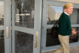 Church overseer Rev. Mike Ware leaves the bullet-riddled entryway of the New Life church in...