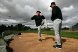 (1915) Coach Jim Wright works on the pitching form of Aaron Cook during Colorado Rockies spring...