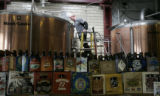 Great Divide brewer, Taylor Rees , tends a brew kettle, as  brewers from more than a dozen...