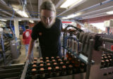 Great Divide bottler , Ben Capron , tends a drop packer on a bottling line at the brewery , as ...