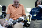 Donald Roberts takes off his new prosthetic arm at Spalding Rehab Hospital in Aurora on Friday,...