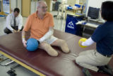 Donald Roberts works out with occupational therapist Tiffany Asbury, right, during a...