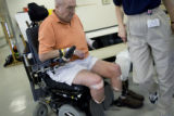Donald Roberts takes a break after walking on his new prosthetic legs at Spalding Rehab Hospital...