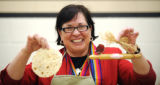 Sister Alicia Cuaron, Centro Bienestar Director, holds her tortilla and trophy after winning a...
