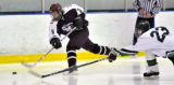 Cheyenne Mountain High School forward Trevor Isbell (left) controlled a puck against Summit High...