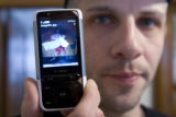 Daniel Gray shows a photo on his cell phone of blood on the floor of his Chicago apartment where...