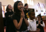 St. Louis Catholic School student Eden Macaraeg, 8, prays while Father Robert Reycraft gets ready...
