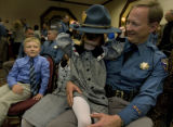 Trooper Doug Wiersma of Pagosa Spgs. watches as his daughter  Joy, 3 tries to wear his hat with...