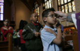 Loyola Grade School student Luke Trujillo, 6, celebrates Ash Wednesday with the rest of his...