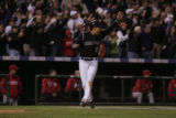 The Colorado Rockies' Yorvit Torrealba cheers on Kazuo Matsui as Matsui goes to third on his...