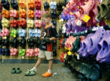 Wyatt Dessel, 7, tries on various pairs of Crocs brand sandals at the Pedestrian Shop in Boulder,...