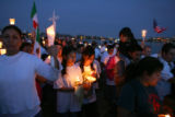 "Pro-immigrant groups hold a candlelight vigil at Sloan's Lake in Denver during a ""National..."