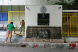 Workers at the Immigration Detention Center in Bangkok sweep the entrance of the center before...