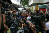 Journalists gather around Lt. Gen. Suwat Tumrongsiskul, head of the Thai immigration police, to...