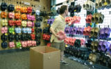 Steve Fagin, general manager of the Pedestrian Shop, stocks the shelves with Crocs brand sandals....