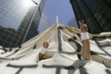A protester gives the peacee sign through a hole in a banner in downtown as over 75,000 rallied...