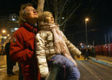 Frediano Costa, left, holds his daughter, Andrea Costa, 9, as they watch jets of flame erupt from...