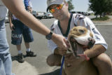 Byron Wood (cq) of Aurora, holds his son's dog, T-Bone, a pit bull, in the parking lot outside the...
