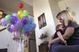 Melissa Givens, 28, holds her youngest son Carson Givens, 10 months, next to a bunch of balloons...