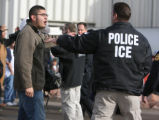 Family members of workers and ICE agents face off after a raid Tuesday Dec. 12, 2006 at the Swift...