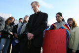 Father Bernie Schmitz, cq, of Are Lady of Pearl in Greeley holds prayer with family members of...