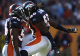 (Denver, Col, September 26, 2004)  Terry Pierce and Patrick Chukwurah celebrate after a hard hit...