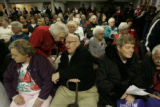 [JD395] Adel, Iowa, caucus goers Wilma McManus (cq), second from the left, whispers something to...